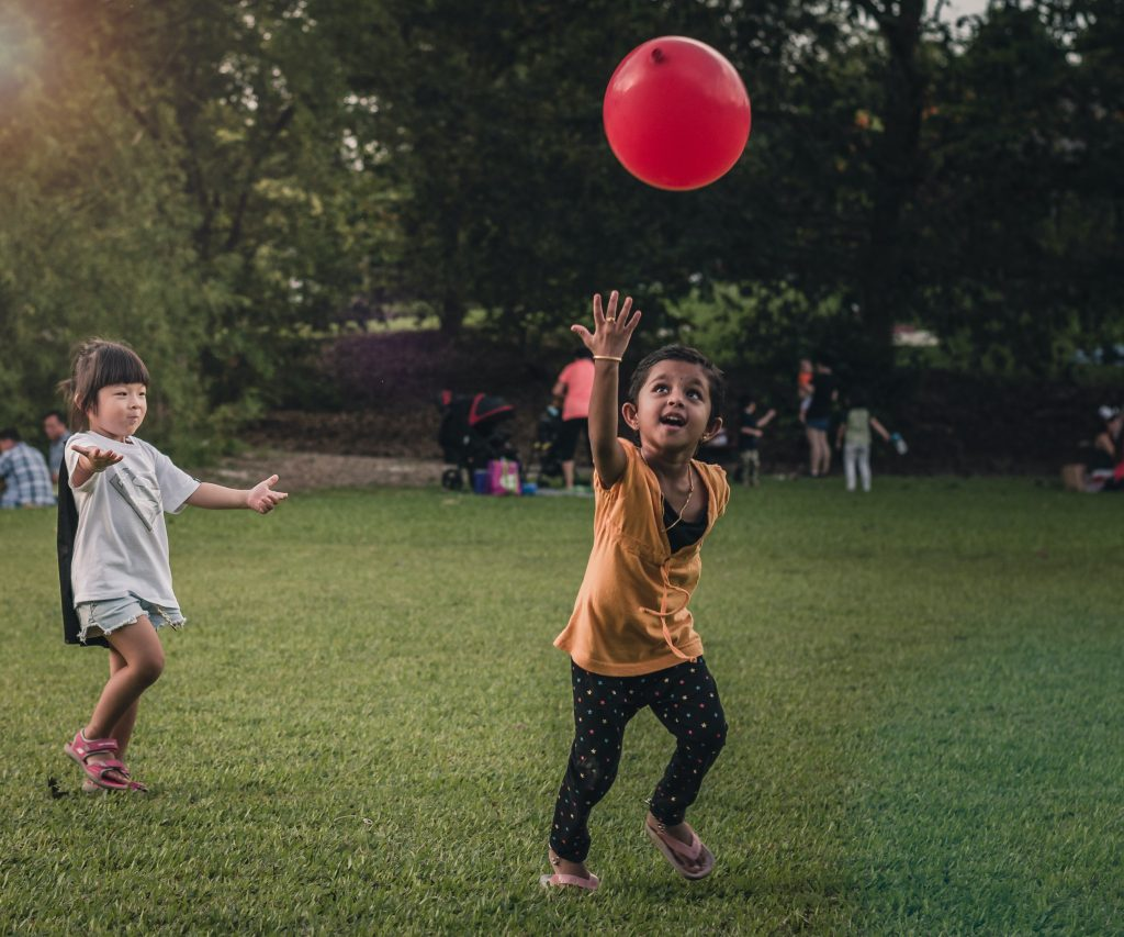 kids playing balloon volleyball outside
